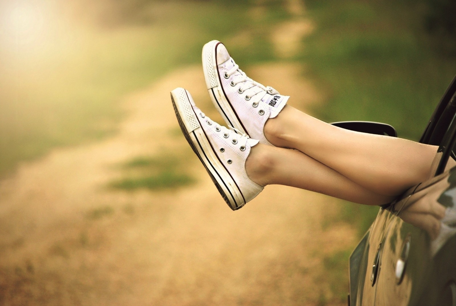 woman-in-canvas-shoes-relaxing-in-car-on-dirt-road